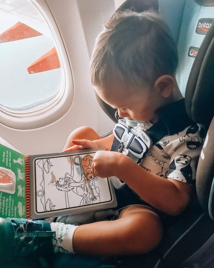 Child on a plane coloring an activity book.