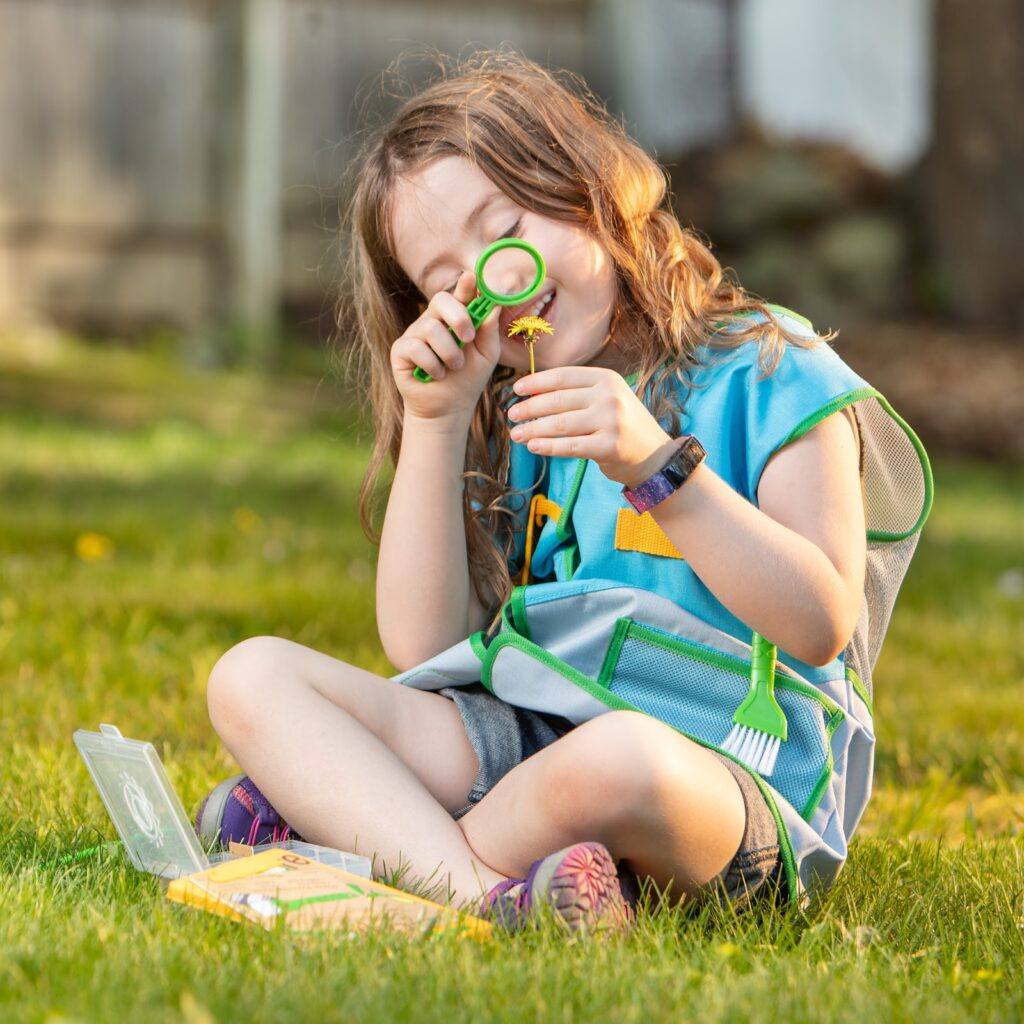 A child uses a magnifying glass to look at a flower.