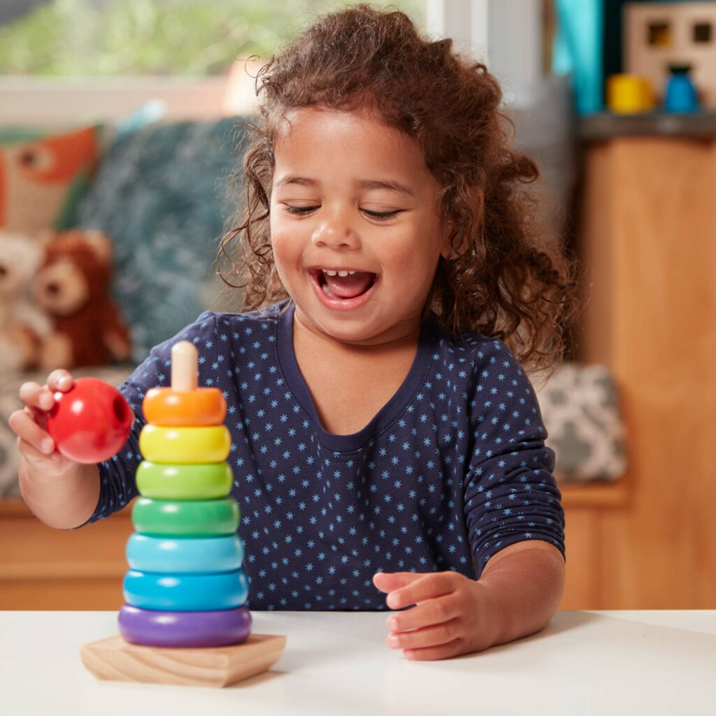 Child playing with Melissa & Doug Rainbow Stacker wooden toy