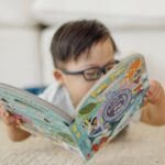 Child wearing glasses and reading Melissa & Doug Poke-A-Dot book