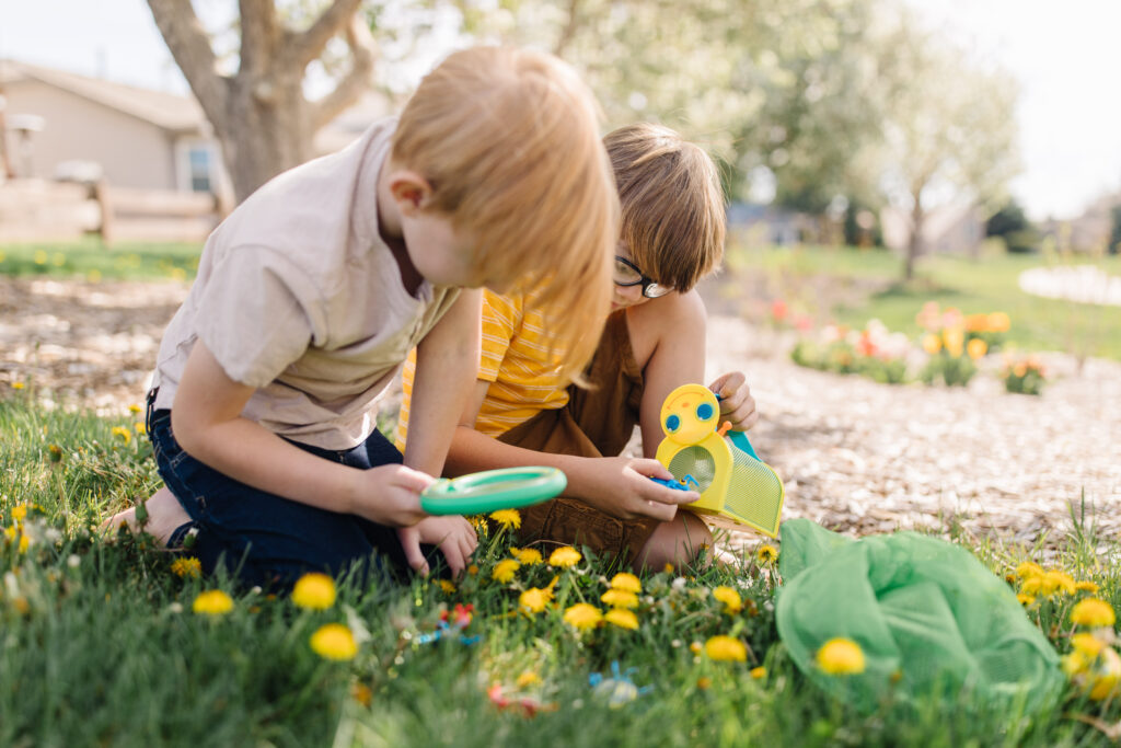 Kids looking at flowers with a Melissa & Doug magnifying glass