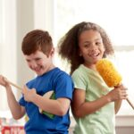 Two kids using Melissa & Doug Dust! Sweep! Mop! toy as pretend musical instruments