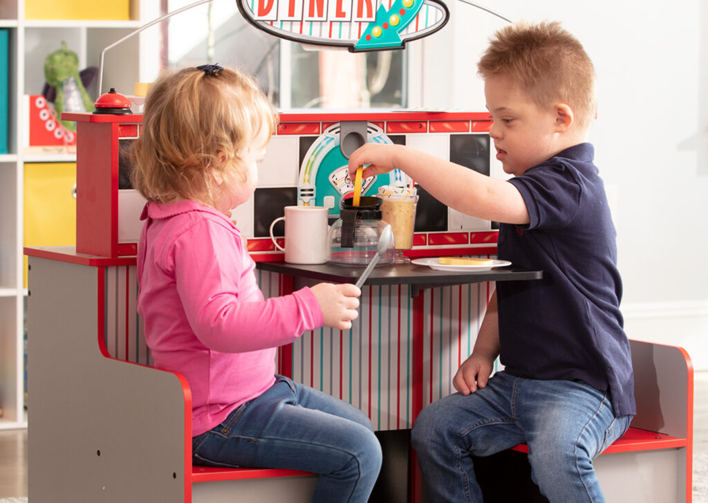 Two kids seated at the Melissa & Doug diner play space