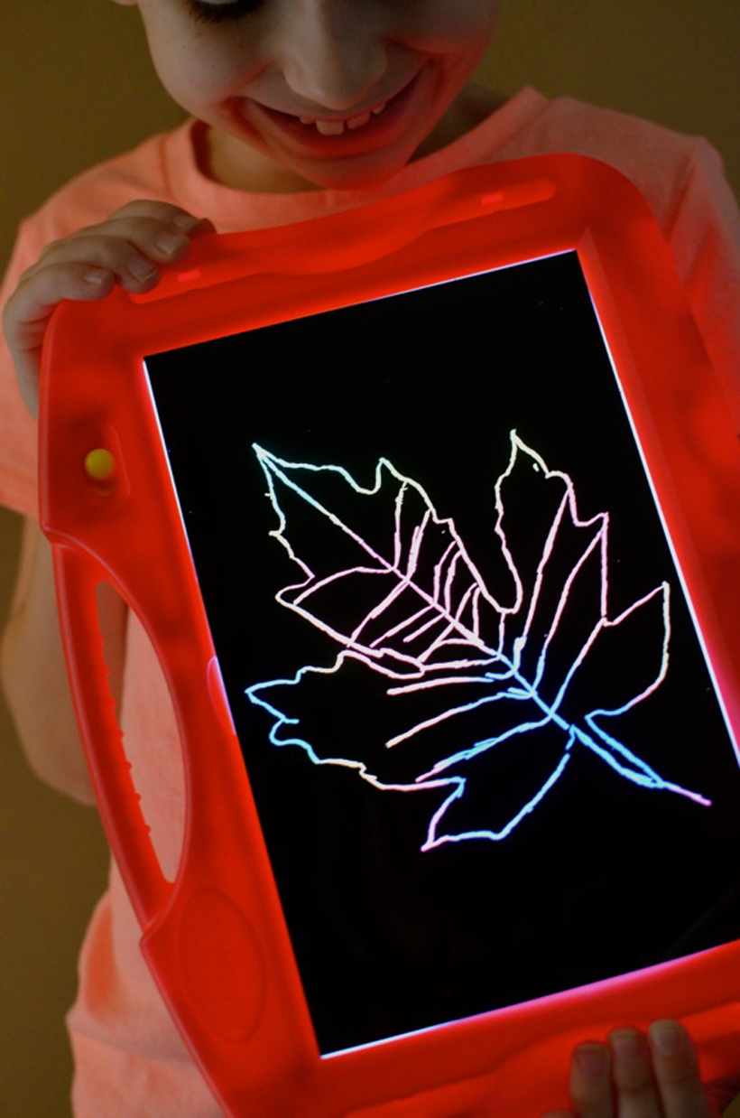 Scratch Art Leaves child displaying masterpiece